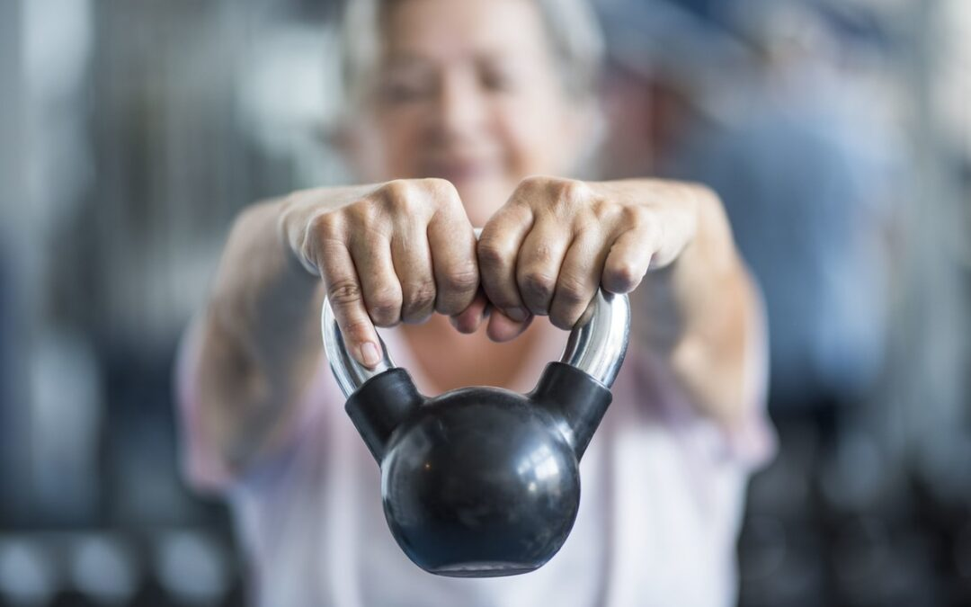Older lady lifting a kettlebell